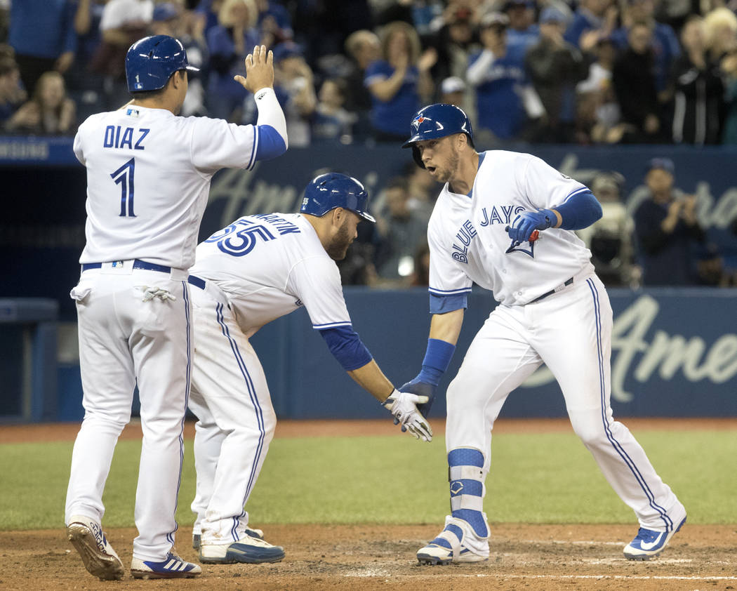 Toronto Blue Jays' Justin Smoak, right, is greeted at home plate by teammates Aledmys Diaz and Russell Martin after he hit a grand slam against the New York Yankees during the eighth inning of a b ...