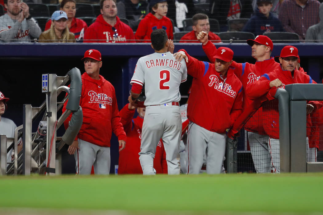 Philadelphia Phillies shortstop J.P. Crawford (2) celebrates with teammates after scoring in the eleventh inning of a baseball game against the Atlanta Braves, Friday, March 30, 2018, in Atlanta.  ...