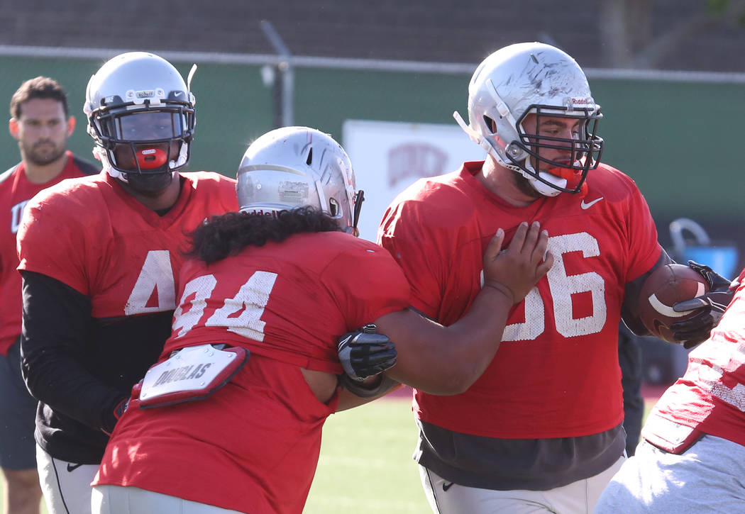 UNLV defensive tackle Kolo Uasike (94) tackles Ammir Aziz (66) during team practice on Monday, April 9, 2018, in Las Vegas. Bizuayehu Tesfaye/Las Vegas Review-Journal @bizutesfaye