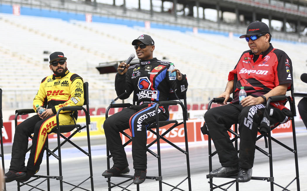 Antron Brown, driver of the Matco Tools/U.S. Army dragster, center, talks about the new track at The Strip at Las Vegas Motor Speedway ahead of the DENSO Spark Plugs NHRA Nationals in Las Vegas on ...