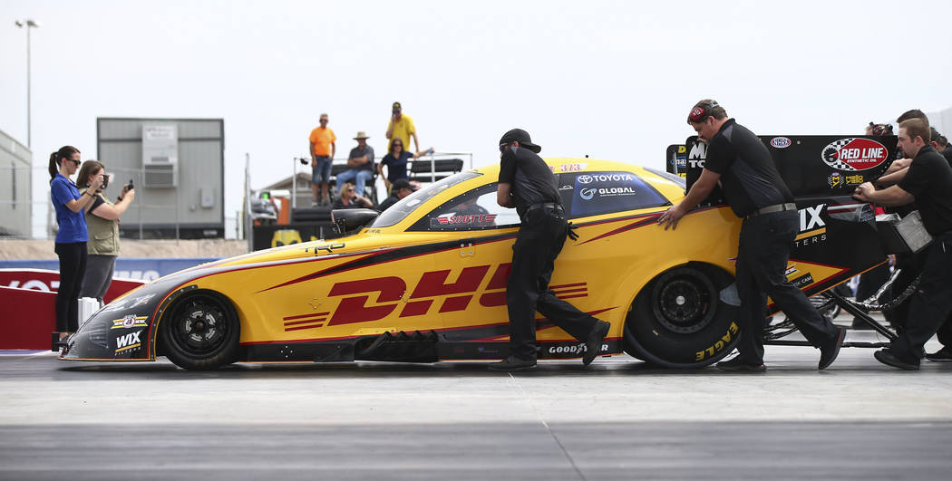 The crew of J.R. Todd, driver of the DHL Toyota Camry Funny Car, move the car at The Strip at Las Vegas Motor Speedway ahead of the DENSO Spark Plugs NHRA Nationals in Las Vegas on Thursday, April ...