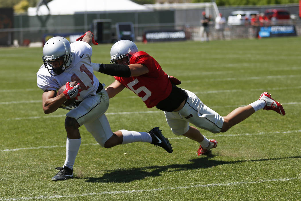UNLV'S wide receiver Drew Tejchman (11) is tackled by defensive back Soli Afalava (15) during UNLV's spring football game at the Peter Johann Memorial Field in Las Vegas on Saturday, April 14, 201 ...