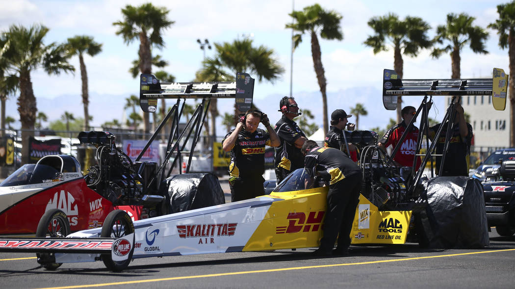 Crew members of Top Fuel driver Richie Crampton prepare for the second day of qualifying for the DENSO Spark Plugs NHRA Nationals at The Strip at Las Vegas Motor Speedway in Las Vegas on Saturday, ...