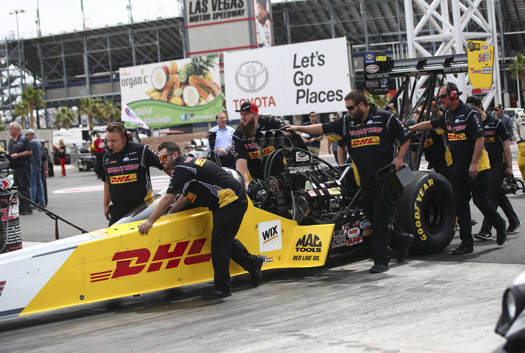 Crew members for Richie Crampton, driver of the Kalitta Air dragster, prepare for a burnout at The Strip at Las Vegas Motor Speedway ahead of competing in the DENSO Spark Plugs NHRA Nationals in L ...