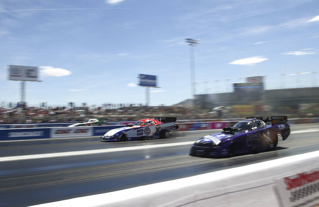 Funny Car drivers Robert Hight, center, and Jack Beckman, right, compete during the second day of qualifying for the DENSO Spark Plugs NHRA Nationals at The Strip at Las Vegas Motor Speedway in La ...