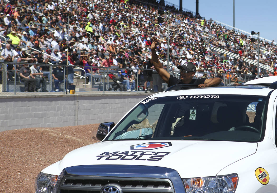 Top Fuel driver Antron Brown acknowledges the crowd after competing during the second day of qualifying for the DENSO Spark Plugs NHRA Nationals at The Strip at Las Vegas Motor Speedway in Las Veg ...