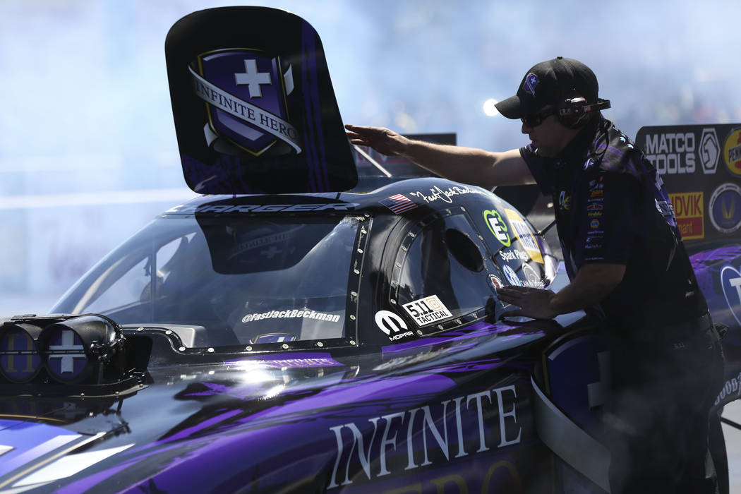 A crew member of Funny Car driver Jack Beckman checks the car during the second day of qualifying for the DENSO Spark Plugs NHRA Nationals at The Strip at Las Vegas Motor Speedway in Las Vegas on  ...