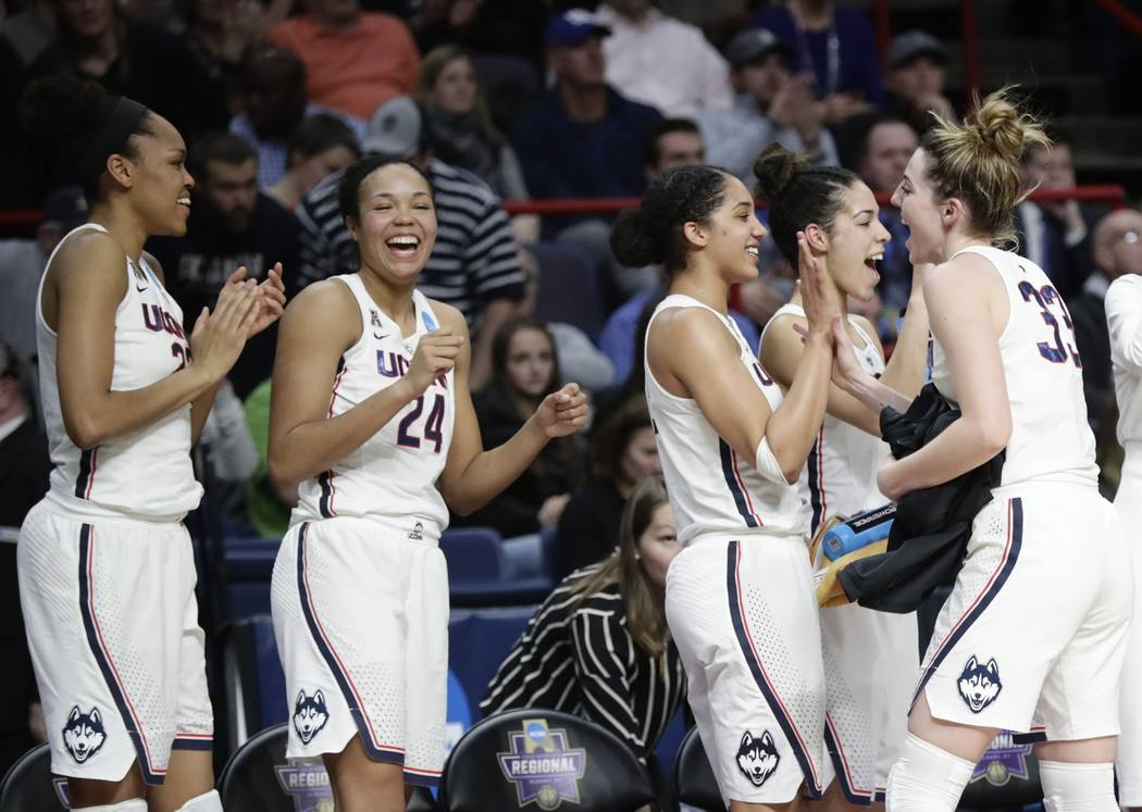 Connecticut's Azura Stevens, left, watches as Napheesa Collier, second from left, Gabby Williams, center, and Kia Nurse celebrate with Katie Lou Samuelson, right, during the second half of a regio ...