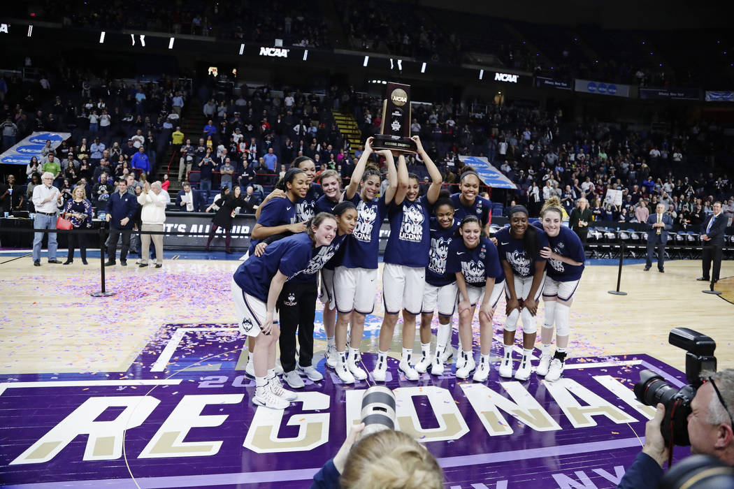 Connecticut players pose for photographs with the regional championship trophy as they celebrate following a women's NCAA college basketball tournament regional final game against South Carolina,  ...