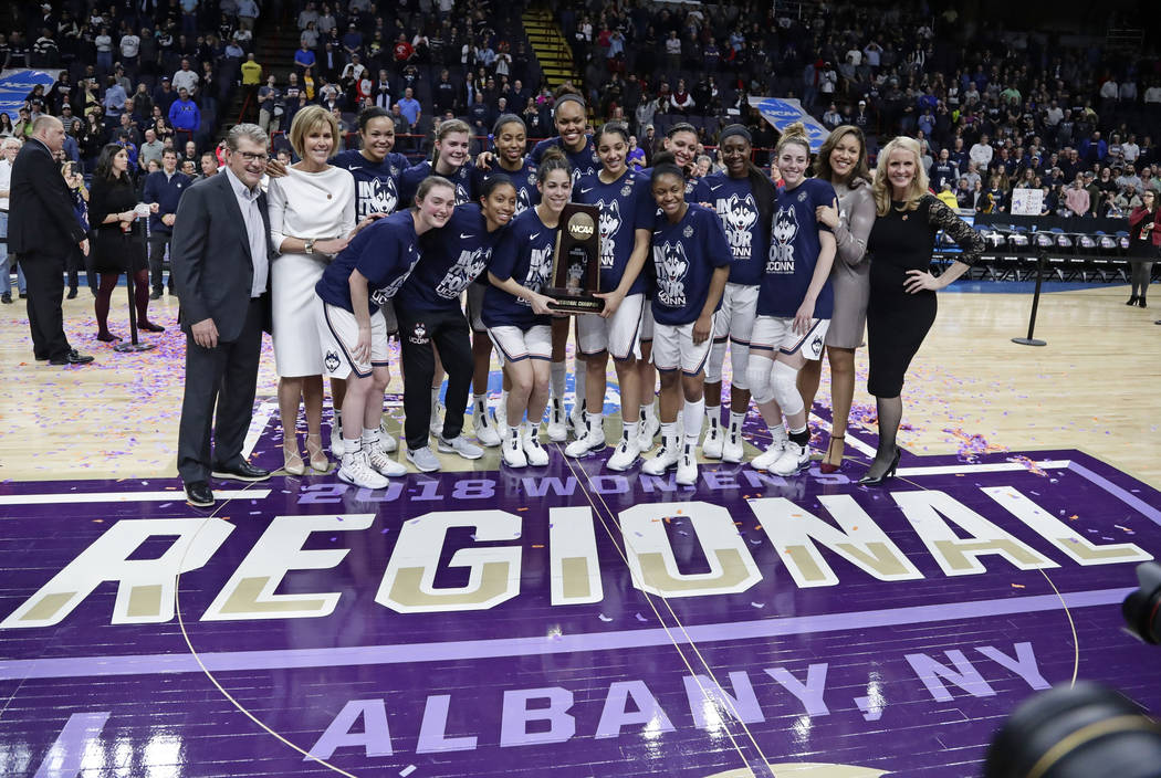 Connecticut head coach Geno Auriemma, left, poses for photographs with with his team following a women's NCAA college basketball tournament regional final game against South Carolina at the a wome ...