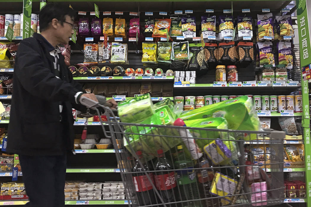 A man pushes a shopping cart past a display of nuts imported from the United States and other countries at a supermarket in Beijing, Monday, April 2, 2018.  China raised import duties on a $3 bill ...