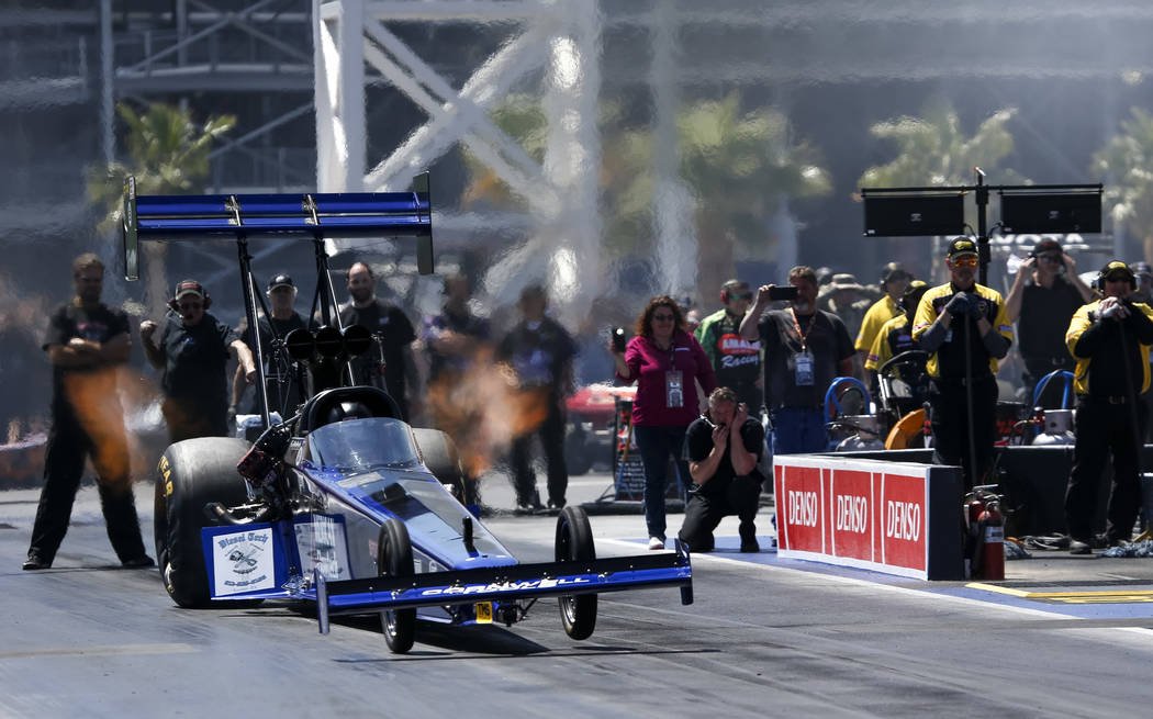 A Top Fuel dragster driven by Terry Haddock takes off from the starting line during the first round of final eliminations on the final day of the DENSO Spark Plug NHRA Four-Wide Nationals at The S ...
