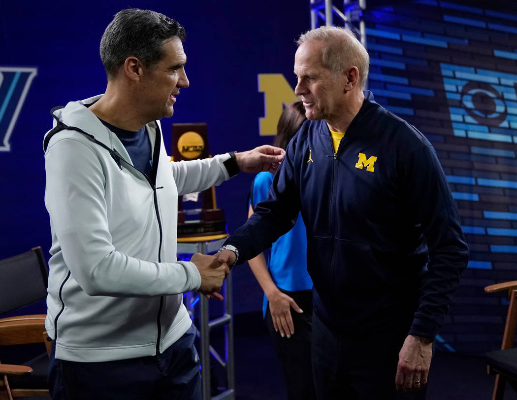 """Villanova head coach Jay Wright, left, and Michigan head coach John Beilein greet each other after an interview for CBS Sports Network's """"We Need to Talk"""" show before the championship ga ..."""