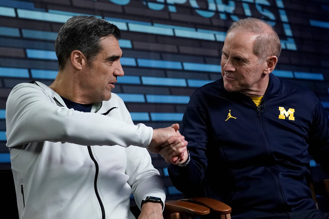 """Villanova head coach Jay Wright, left, and Michigan head coach John Beilein shake hands during an interview for CBS Sports Network's """"We Need to Talk"""" show before the championship game o ..."""