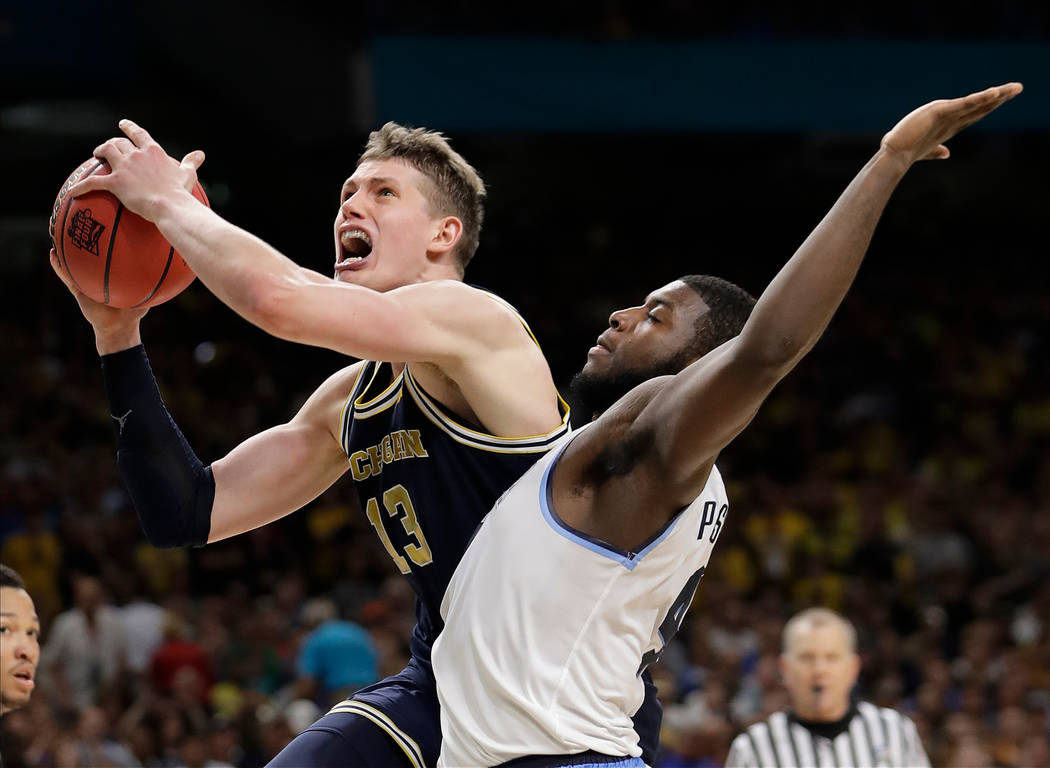 Michigan's Moritz Wagner (13) shoots over Villanova's Eric Paschall (4) during the second half in the championship game of the Final Four NCAA college basketball tournament, Monday, April 2, 2018, ...