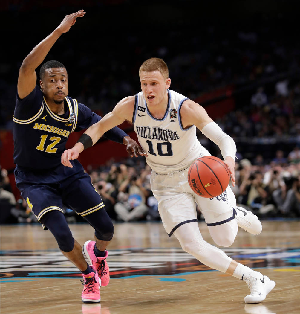 Villanova's Donte DiVincenzo (10) drives past Michigan's Muhammad-Ali Abdur-Rahkman (12) during the first half in the championship game of the Final Four NCAA college basketball tournament, Monday ...
