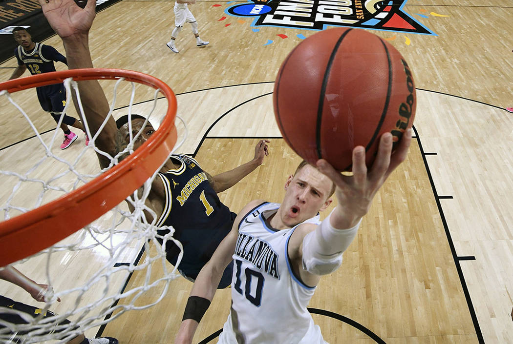 Villanova's Donte DiVincenzo (10) goes up for a shot past Michigan's Charles Matthews (1) during the second half in the championship game of the Final Four NCAA college basketball tournament, Mond ...