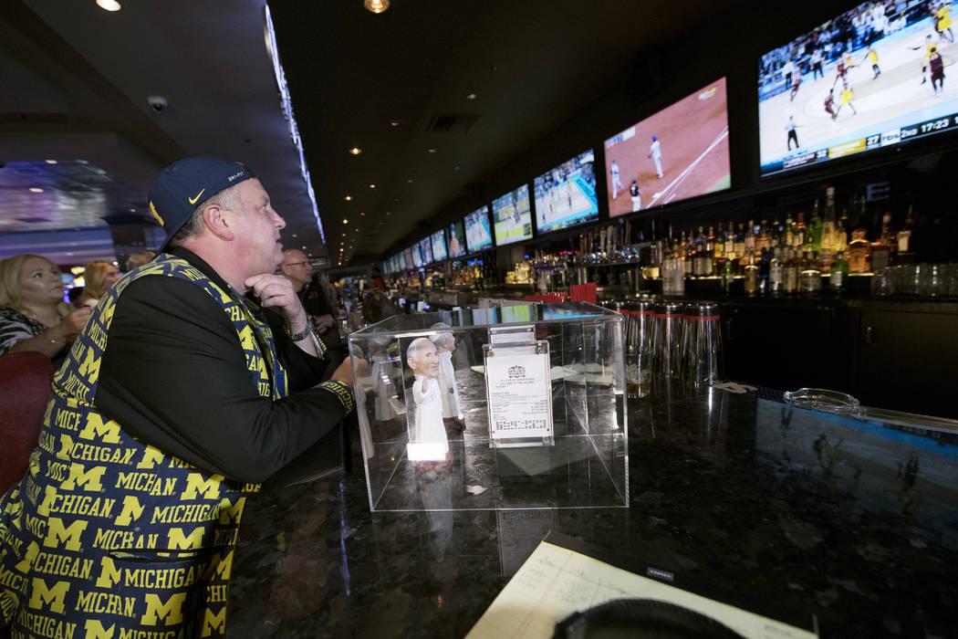 Derek Stevens, CEO and co-owner of The D Las Vegas, watches as his alma mater Michigan takes on Loyola in the Final Four Saturday, March 31, 2018, at The D. Next to him is his betting slip encased ...