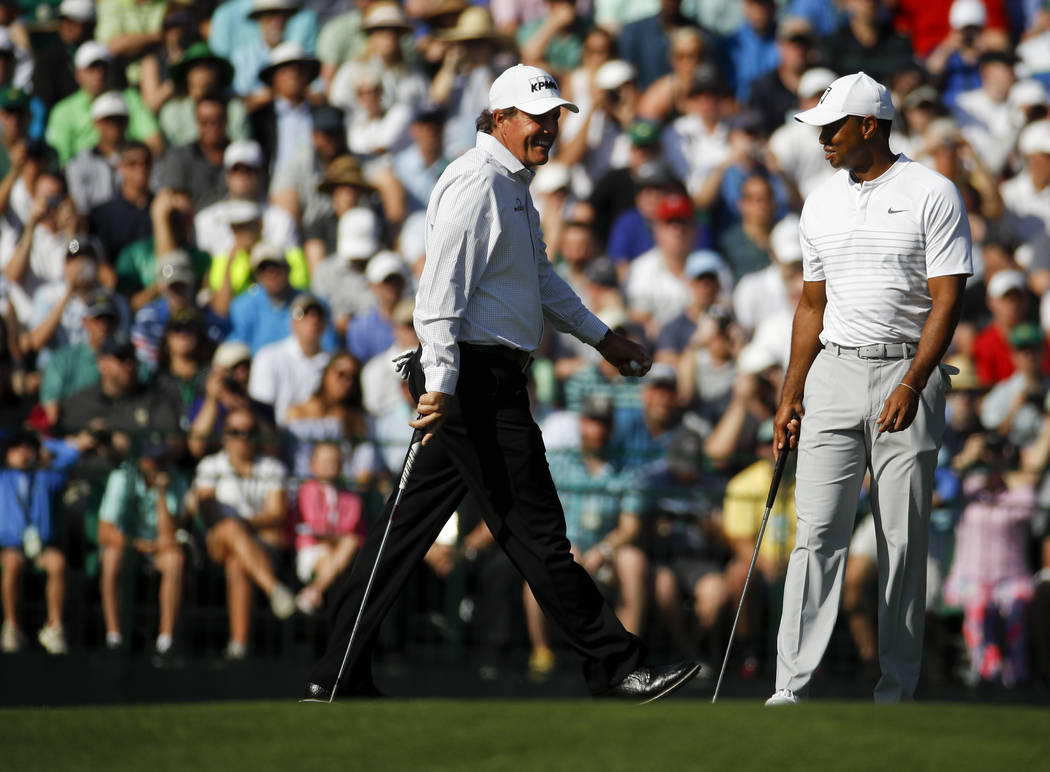 Phil Mickelson, left, and Tiger Woods chat on the 15th hole during practice for the Masters golf tournament at Augusta National Golf Club, Tuesday, April 3, 2018, in Augusta, Ga. (AP Photo/Charlie ...