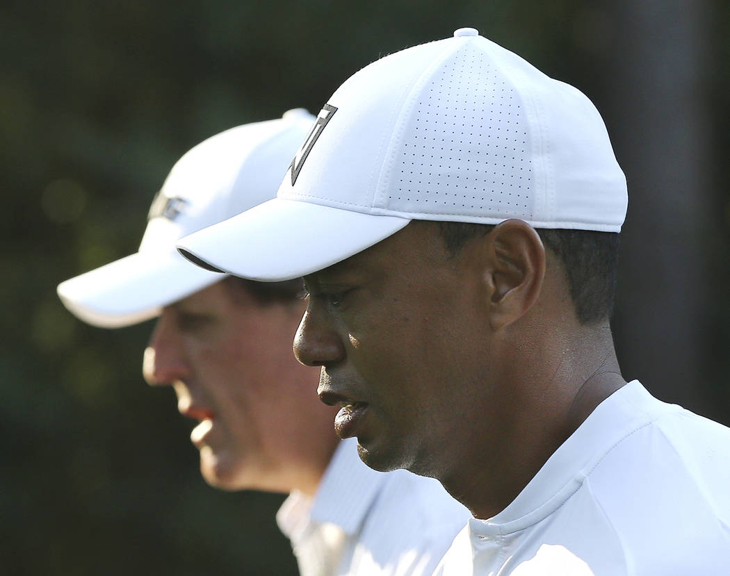 Phil Mickelson, left, and Tiger Woods walk down the 11th fairway while playing a practice round for the Masters golf tournament at Augusta National Golf Club in Augusta, Ga., Tuesday, April 3, 201 ...