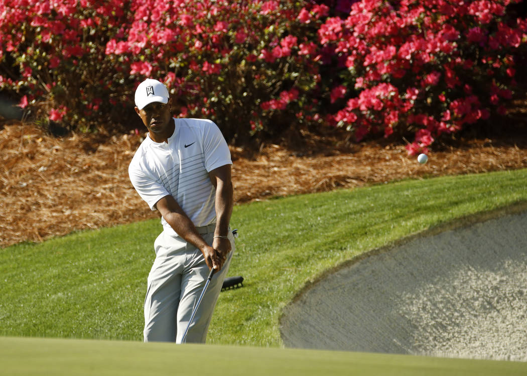 Tiger Woods hits a chip on the 13th hole during practice for the Masters golf tournament at Augusta National Golf Club, Tuesday, April 3, 2018, in Augusta, Ga. (AP Photo/Charlie Riedel)