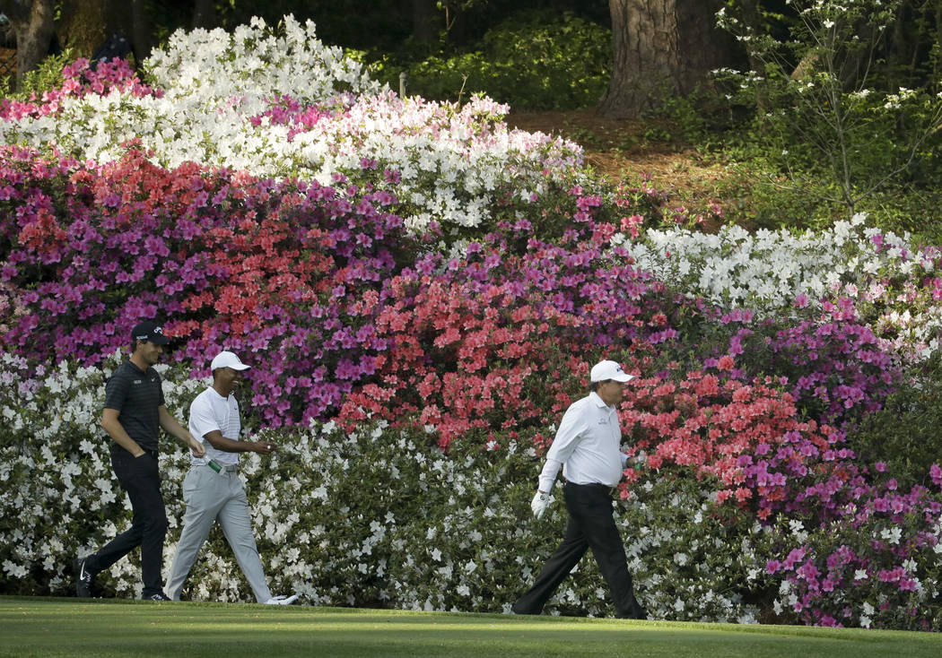 Phil Mickelson, from right, Tiger Woods and Thomas Pieters, of Belgium, walk to the 13th fairway during practice for the Masters golf tournament at Augusta National Golf Club, Tuesday, April 3, 20 ...