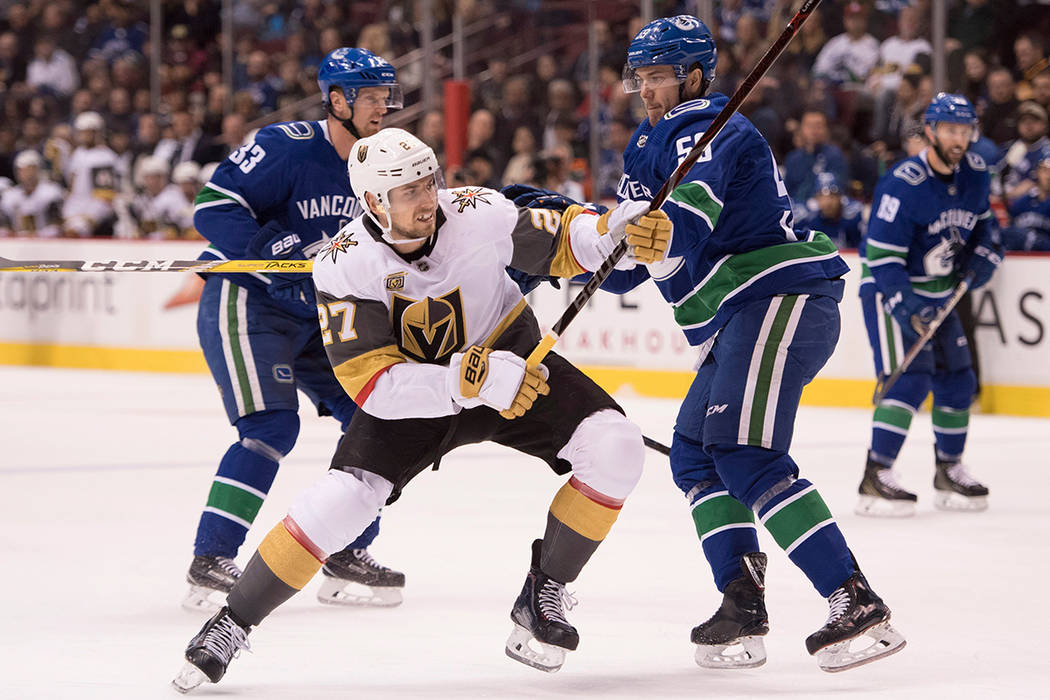 Vegas Golden Knights defenseman Shea Theodore (27) fights for control of  the puck with cf538ded4