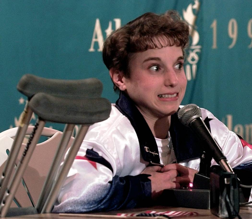USA's Kerri Strug, of Houston, Texas, reacts to a reporter's question during a news conference before the women's all-around competition at the Centennial Summer Olympic Games in Atlanta on Thursd ...