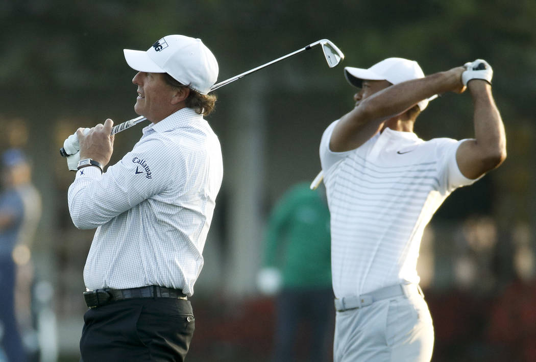 Phil Mickelson, left, and Tiger Woods warm up on the driving range during practice for the Masters golf tournament at Augusta National Golf Club, Tuesday, April 3, 2018, in Augusta, Ga. (AP Photo/ ...