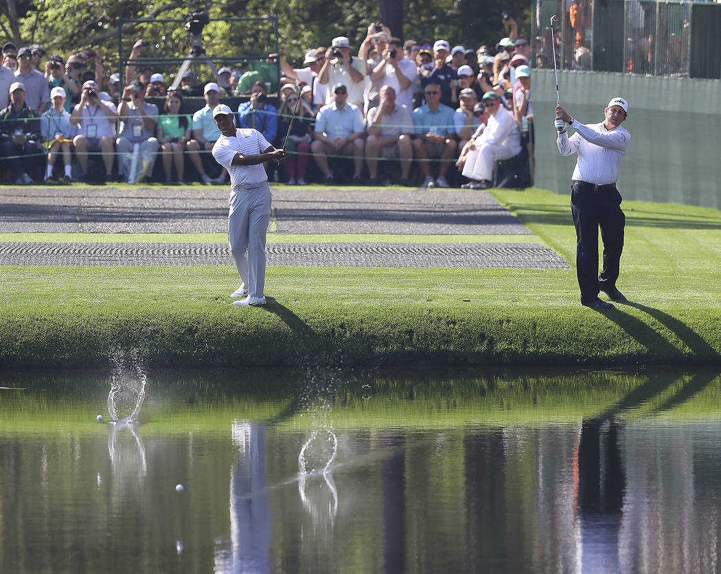 Tiger Woods, left, and Phil Mickelson skip their shots across the pond to the 16th green while clowning around for the crowd during a practice round for the Masters golf tournament at Augusta Nati ...