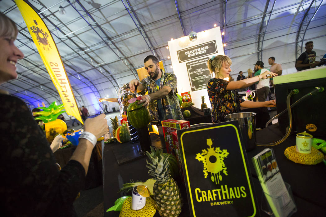 CraftHaus Brewery Head Brewers Steve Brockman, center left, and Steph Cope pour beers for attendees during the Mad Craft event as part of the Great Festival of Beer at the World Market Center in L ...