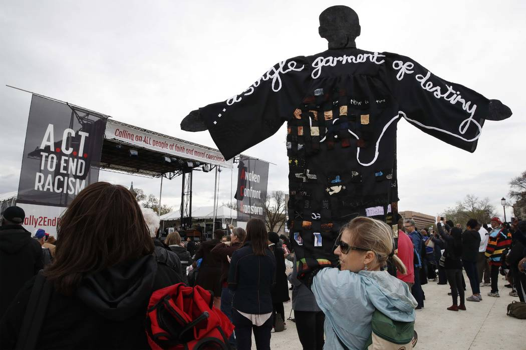 Molly Jackman, of Kensington, Md., holds up a sign with a silhouette of Martin Luther King Jr., while attending the A.C.T. To End Racism rally, Wednesday, April 4, 2018, on the National Mall in Wa ...