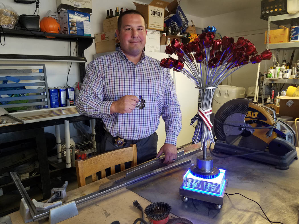 Metropolitan Police Department detective Darryl McDonald, an artist in his spare time, is shown April 4, 2018, at his Las Vegas home with his art piece of 58 metal roses to honor the victims kille ...