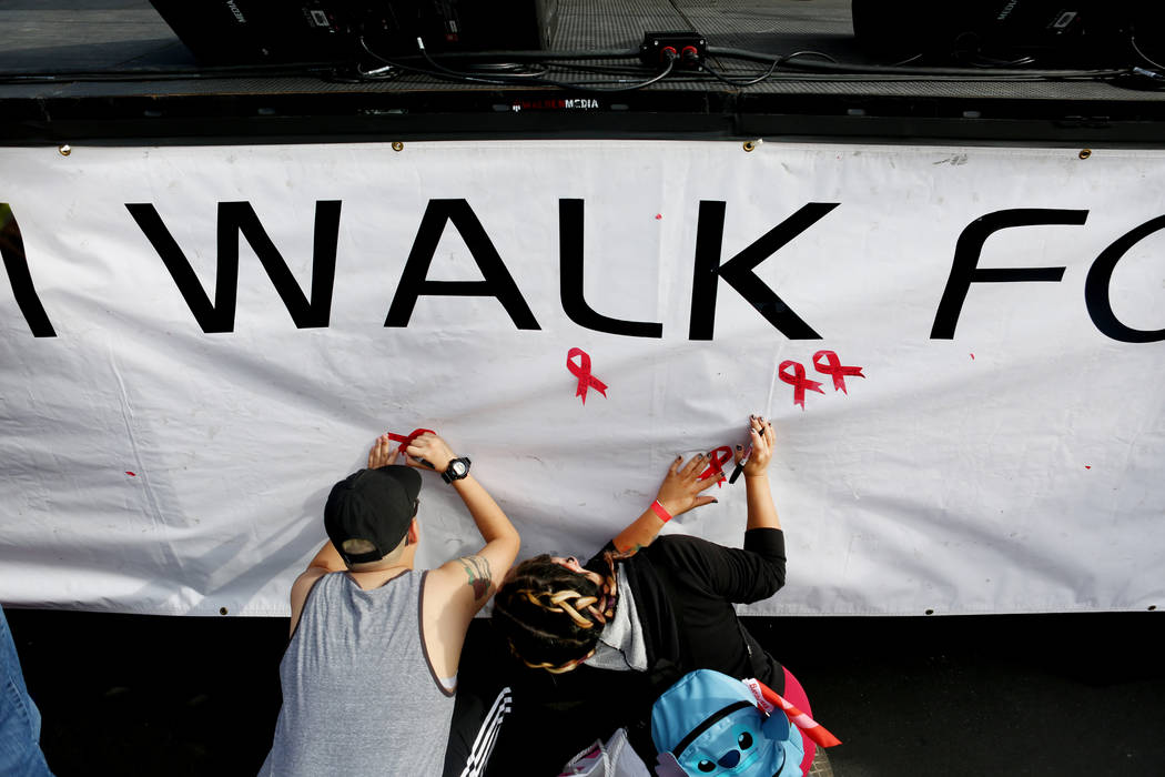 AIDS Walk participants write a friend's name who recently died on a memorial banner during the 27th annual AIDS Walk presented by Aid for AIDS of Nevada, Sunday, April 23, 2017 at Las Vegas Town S ...