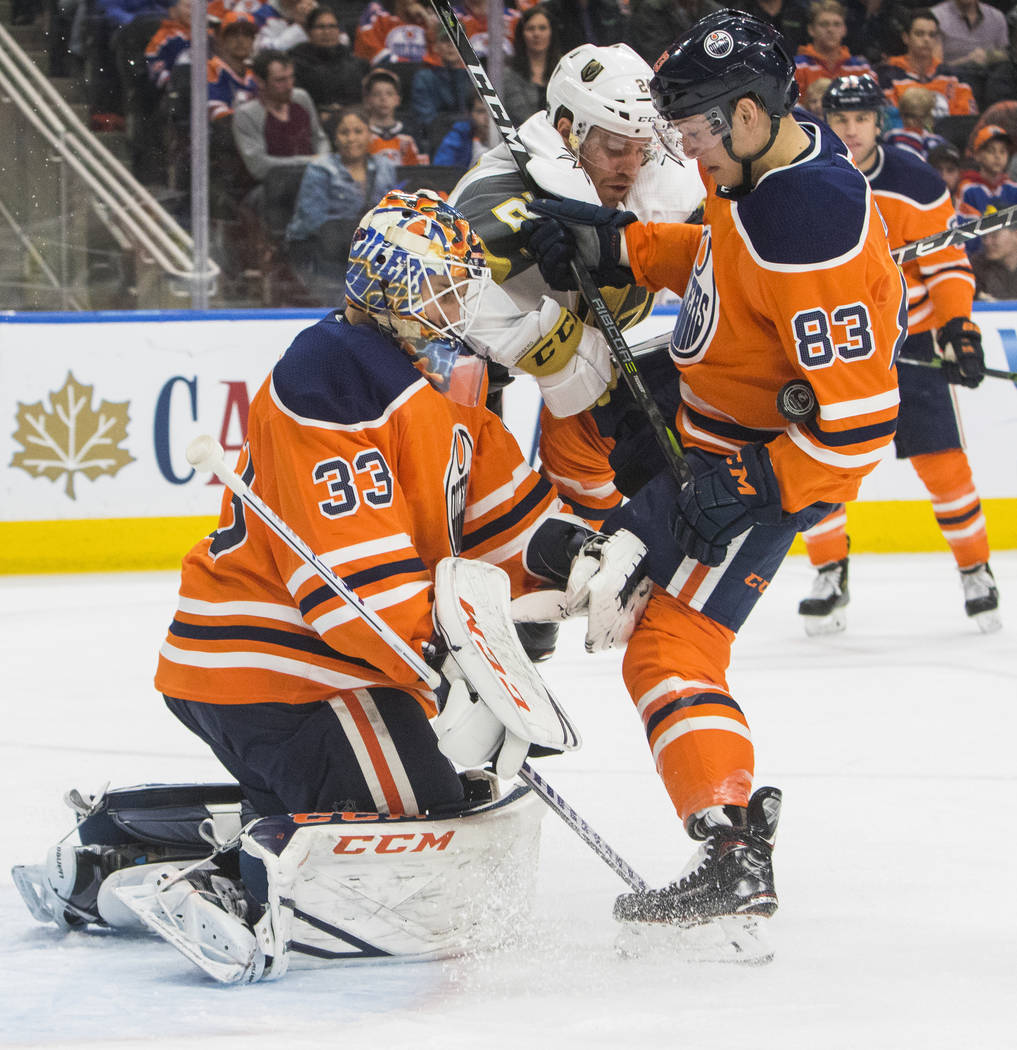 Vegas Golden Knights' Oscar Lindberg (24) looks on as a shot against Edmonton Oilers goalie Cam Talbot (33) is caught up in Matthew Benning's (83) jersey during first-period NHL hockey game action ...