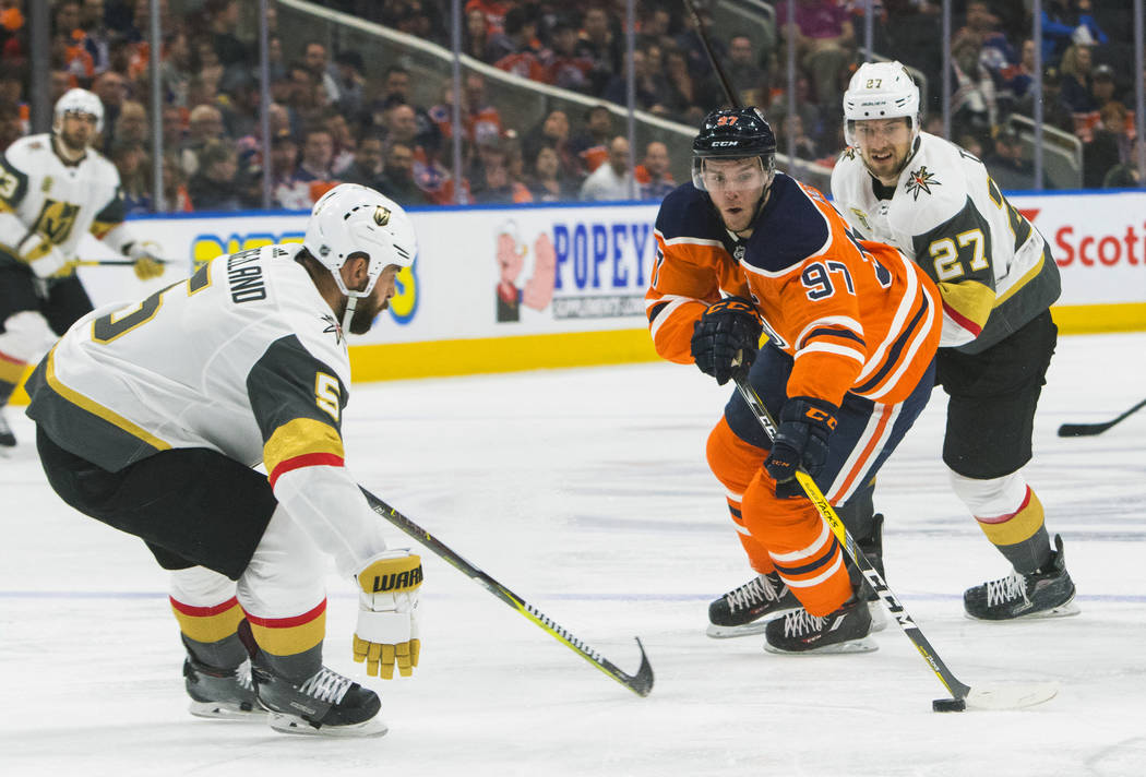 Vegas Golden Knights' Deryk Engelland (5) and teammate Shea Theodore (27) pressure Edmonton Oilers' Connor McDavid (97) during second-period NHL hockey game action in Edmonton, Alberta, Thursday,  ...