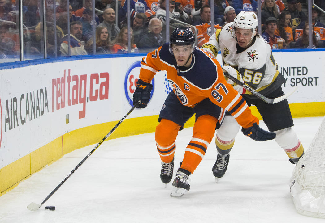 Vegas Golden Knights' Erik Haula (56) pressures Edmonton Oilers' Connor McDavid (97) during second-period NHL hockey game action in Edmonton, Alberta, Thursday, April 5, 2018. (Amber Bracken/The C ...