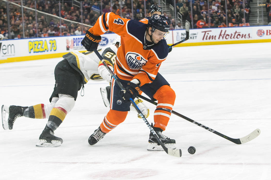 Vegas Golden Knights' Erik Haula (56) looks for the puck against Edmonton Oilers' Kris Russell (4) during first-period NHL hockey game action in Edmonton, Alberta, Thursday, April 5, 2018. (Amber  ...