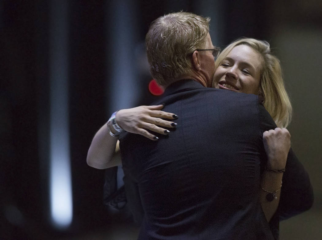 Courtney Humm, right, gets a hug from Steve Stallworth, general manager of South Point Arena & Equestrian Center, during a ceremony to celebrate the life of her father and former local footbal ...