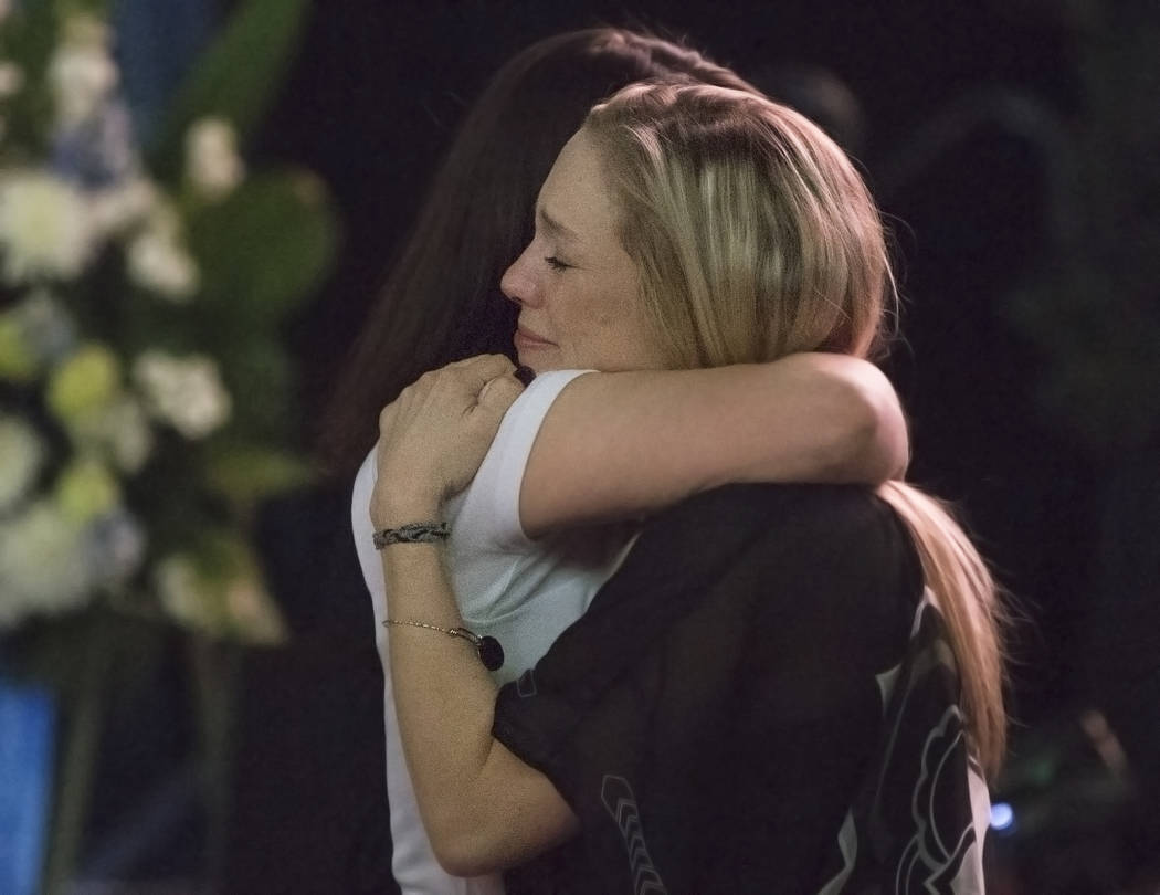 Courtney Humm, right, hugs a friend during a ceremony to celebrate the life of her father and former local football great David Humm on Friday, April 6, 2018, at South Point Arena, in Las Vegas. H ...