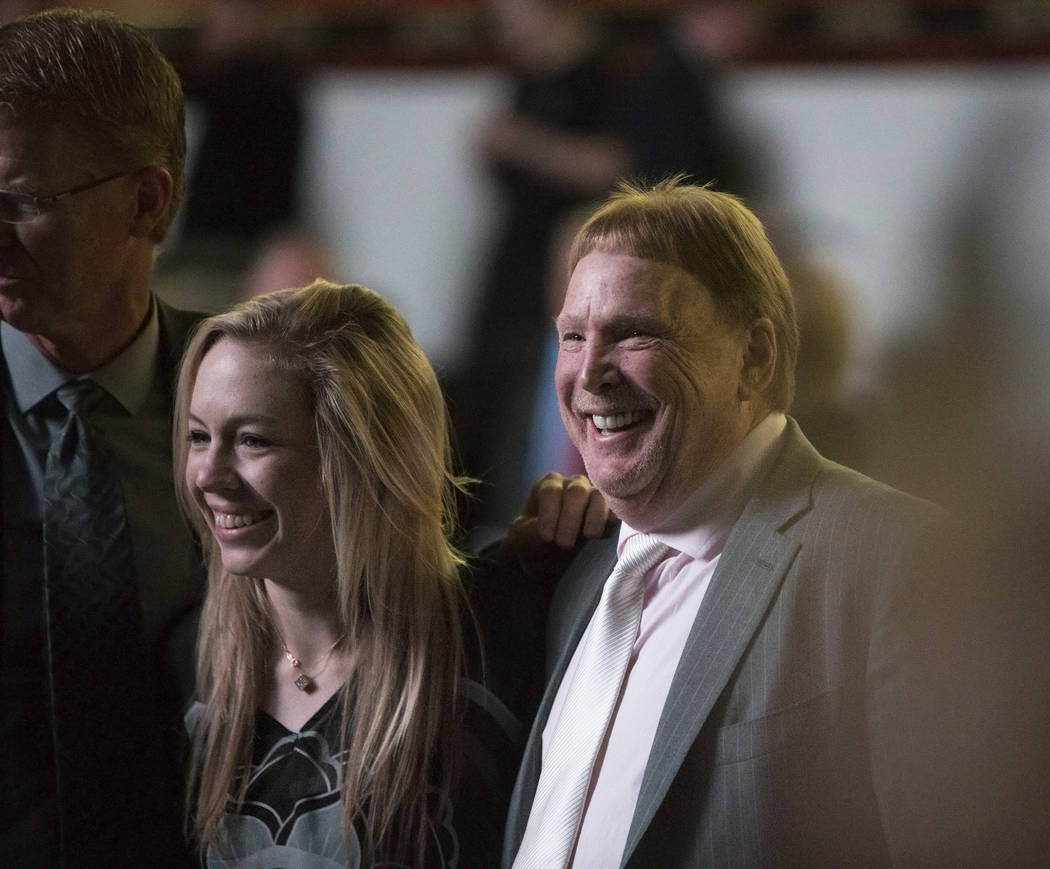 Courtney Humm, left, takes a photo with Mark Davis, owner and managing general partner of the Oakland Raiders, during a ceremony to celebrate the life of her father and former local football great ...