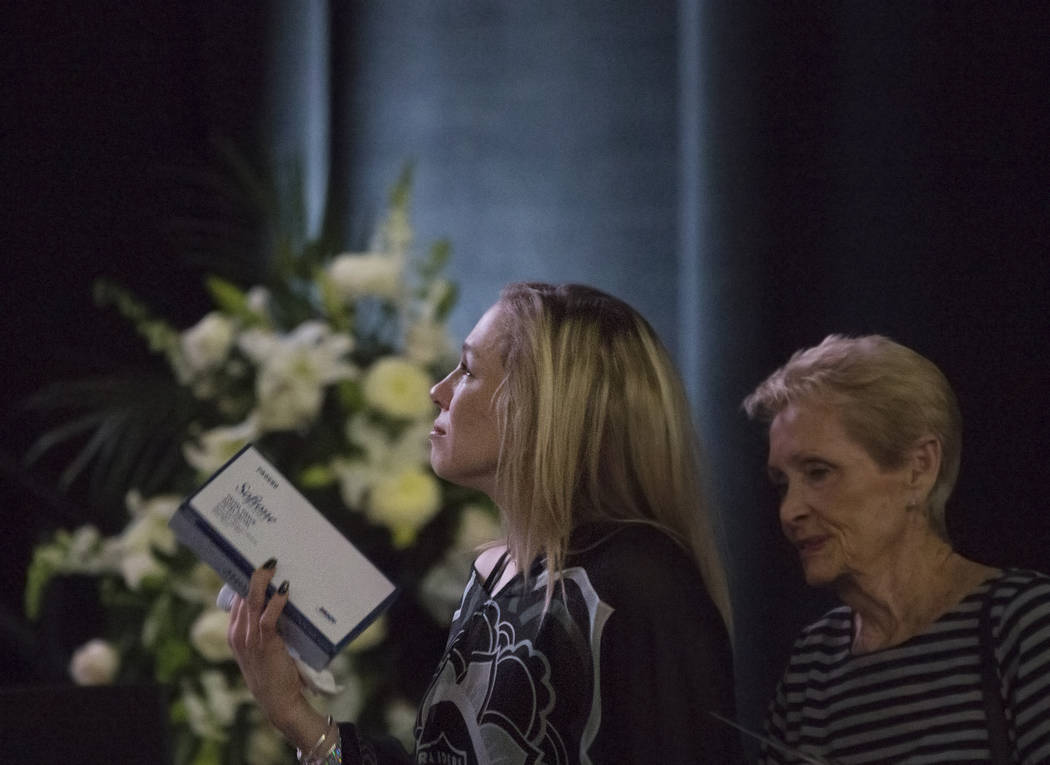 Courtney Humm, left, holds a box of tissues as she listens to a speaker during a ceremony to celebrate the life of her father and former local football great David Humm on Friday, April 6, 2018, a ...
