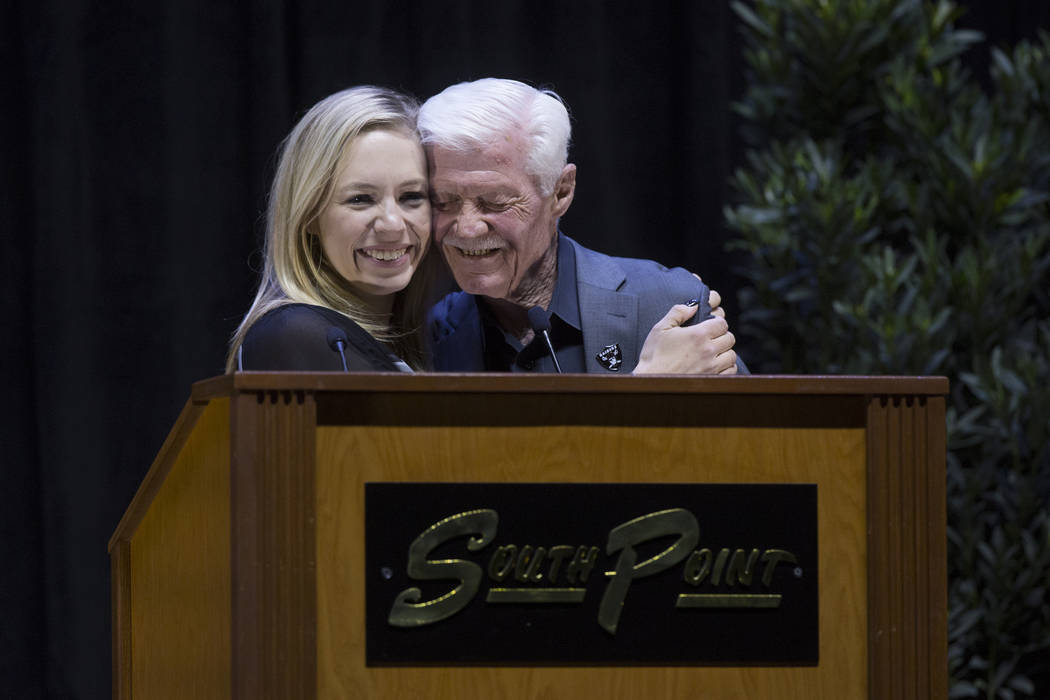 Daughter Courtney Humm, left, and brother Tom Humm share a hug on stage during a ceremony to celebrate the life of former local football great David Humm on Friday, April 6, 2018, at South Point A ...
