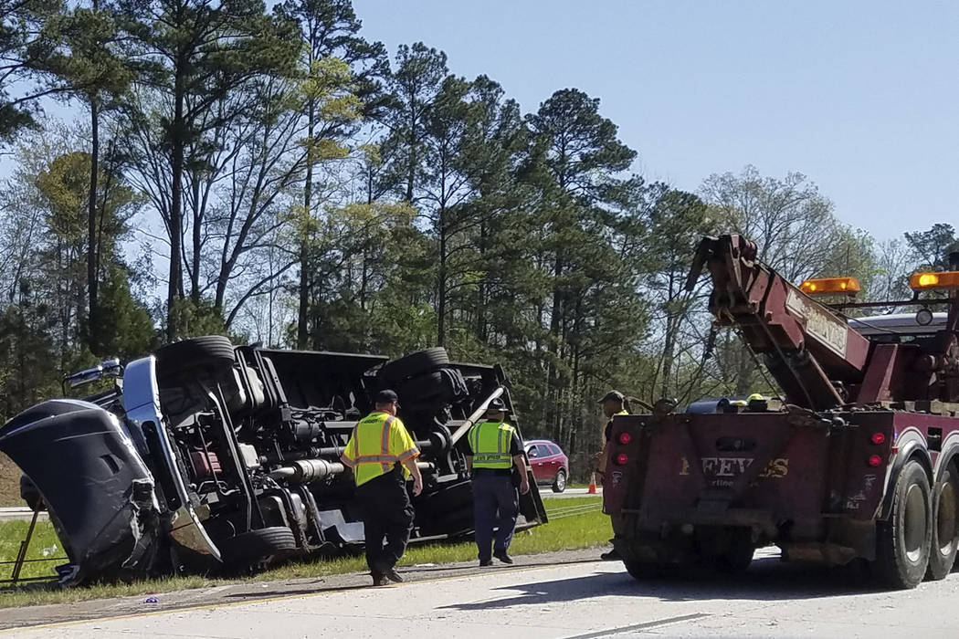 Police officers and emergency workers examine the scene of the accident scene Thursday morning, April 5, 2018, after a tour bus heading to the Masters golf tournament overturned along Interstate 2 ...