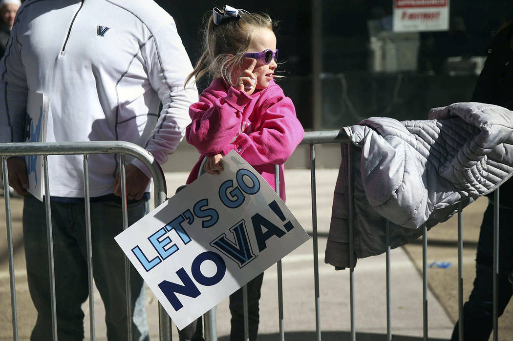 Avery Gergel, 6, of Pottstown, whose father is a Villanova graduate, makes a V sign along Market Street before Villanova's NCAA men's basketball tournament victory parade, Thursday, April 5, 2018, ...