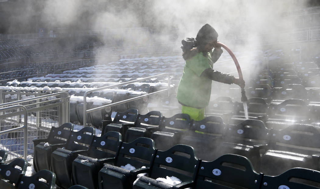A worker is engulfed in steam while using hot water to melt snow in the stands and seats at Target Field in Minneapolis, Wednesday, April 4, 2018, following a snow storm, in preparation for Thursd ...