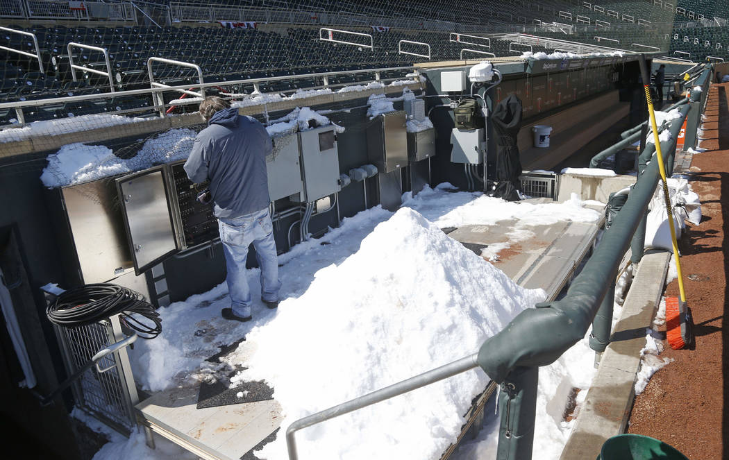 Snow from Tuesday's storm is piled, ready to be removed from the television platform next to the Minnesota Twins dugout at Target Field in Minneapolis Wednesday, April 4, 2018, in preparation for  ...