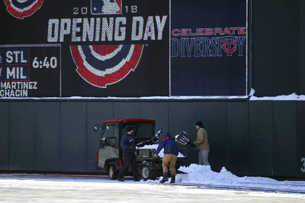 Grounds crew workers remove the remaining snow from Tuesday's storm in right field at Target Field in Minneapolis Wednesday, April 4, 2018, in preparation for Thursday's baseball home opener betwe ...