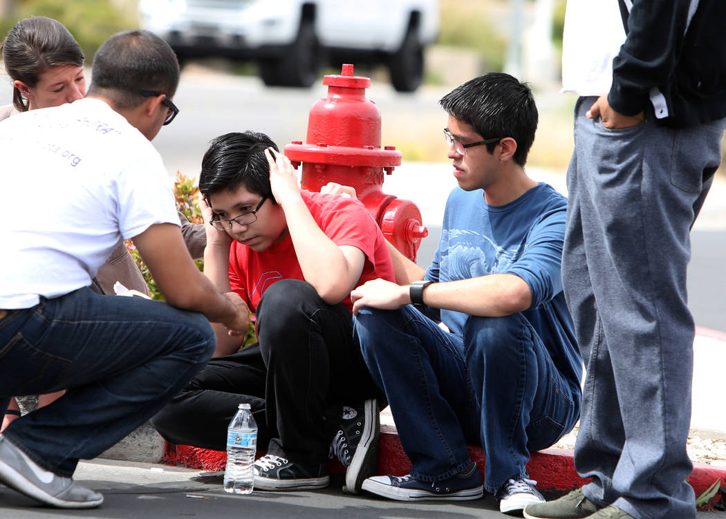 Eric Avelar, 13, center, talks with a cell phone as his brother, Ricardo Avelar, 18, second right, looks on after they held a press conference outside of U.S. Citizen and Immigration Service build ...