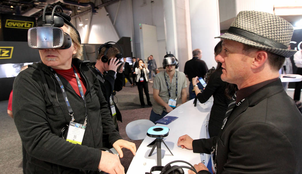 Cliff Hokanson, left, checks out virtual reality content with John Iverson of Humaneyes Technologies during the National Association of Broadcasters Show at the Las Vegas Convention Center Wednesd ...